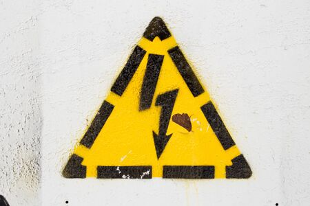 Painted stencil yellow high voltage hazard symbol on the painted gray metal surface.