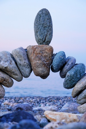 strength in unity: close-up of a handmade stonebridge against sky Stock Photo