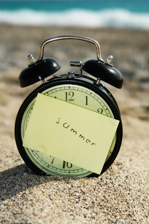 close-up of a clock with a note at a beach photo
