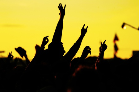 hands in the air: people celebrating on an open air shillouettes