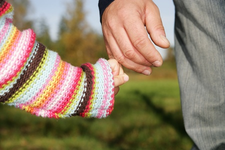 hand grip: A parent holding the hand of its child while walking in a park.