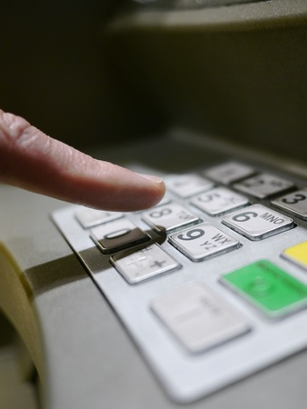 Finger using automatic teller keypad to enter pin number photo