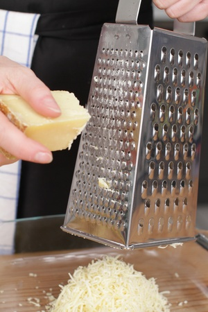 grater: Parmesan cheese with grater on wooden chopping board.