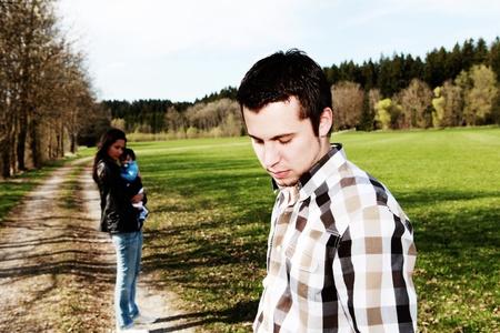печальный: Печально человека, стоящего в стороне от женщины с ребенком, развод