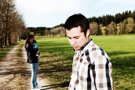 woman sad: hombre triste de pie a un lado de la mujer con el beb�, el divorcio