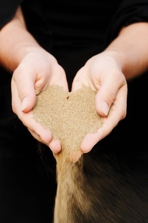 time off: sand running through hands as a symbol for time running, lost etc............. Stock Photo