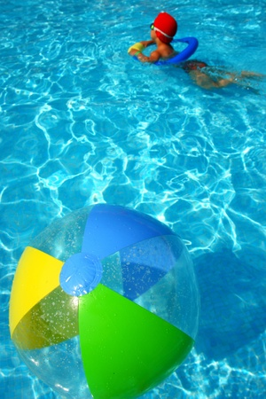 A colorful beach ball floating on the swimming pool. photo