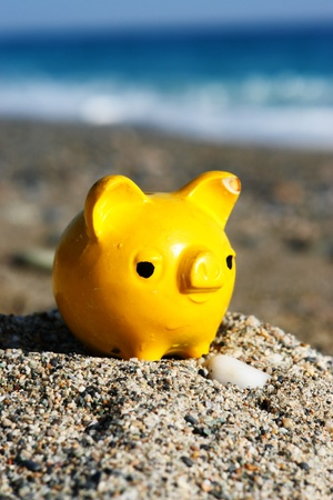 close up of a yellow piggybank on the beach photo
