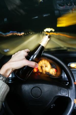 violaci�n: beber cerveza mientras conduc�a el coche Foto de archivo