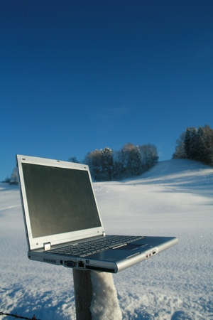 Laptop in a snowy winter landscape scene photo