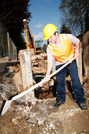 buildingsite: Close-up of a worker digging at building site Stock Photo