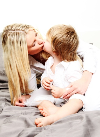 tender tenderness: young mother with her 2 years old son on the bed playing with feathers and pillows....