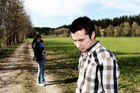 pareja discutiendo: hombre triste de pie a un lado de la mujer con el bebé, el divorcio