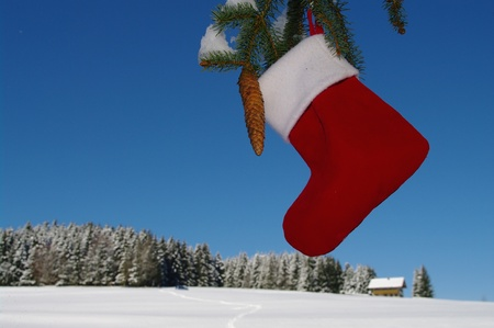 Santa Claus Christmas boot for gifts outside in a snowy landscape photo