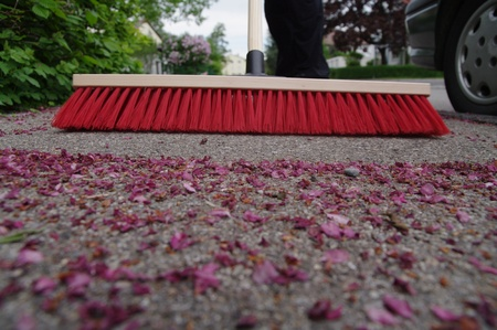 tidying up: sweeping the sidewalk with a broom