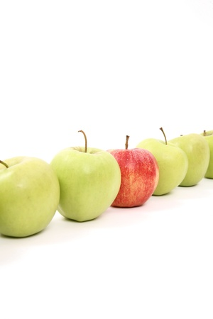 odd one out: apples arranged on a white background to symbolize teamwork, leadership, discrimination............