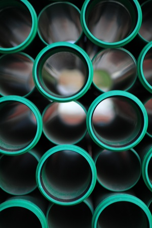 a stack of green pipes in a construction zone