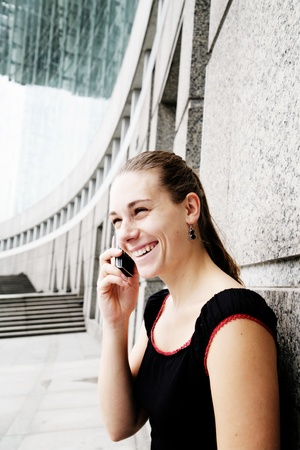 25 29 years: Businesswoman standing outdoors by building on cellular phone (high keyselective focus)