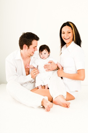 A young happy family with their 4  month old son sitting in bed Stock Photo - 11214047