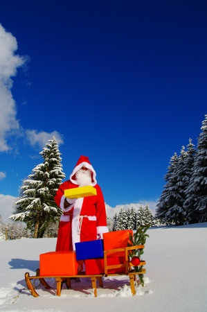 Santa Claus, Father Christmas with colorful presents on a sledge photo