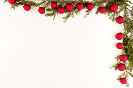 Border of red christmas garland with baubles and ribbons on white. photo