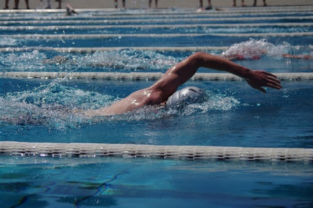Freestyle swimmer in the outdoor swimming pool photo