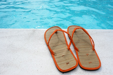 water's edge: Sandals at the pool on a very sunny day Stock Photo