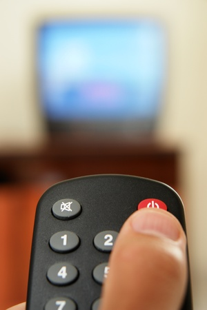 telly: Television screen with tv remote control in foreground Stock Photo