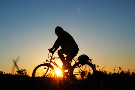 biker on a meadow at the sunset photo