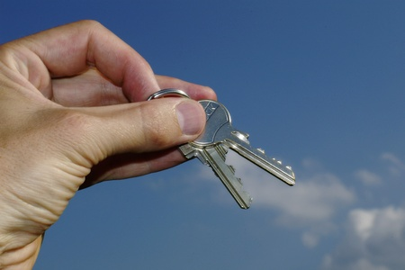 Hand holding keys against blue sky photo