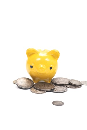 yellow piggy bank with very old coins Stock Photo - 15733775