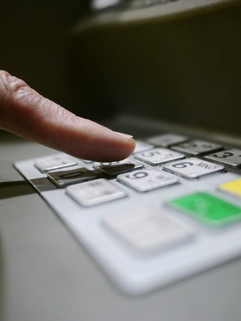 Finger using automatic teller keypad to enter pin number Stock Photo - 15975123