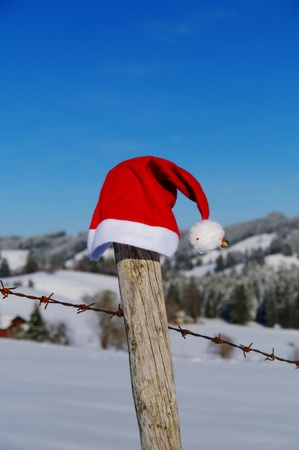 x mas: red santa claus hats in a snowy landscape
