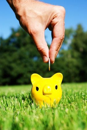 close-up of a yellow piggybank while putting coins inside Stock Photo - 16257173