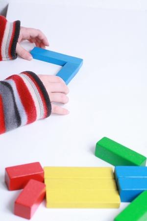 kind handen te spelen geïsoleerde speelgoed met houten blokken