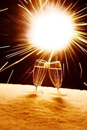 sylvester: two champagne glasses in snow clink glasses for new year on sylvester firework in background
