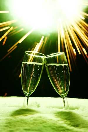 two champagne glasses in snow clink glasses for new year on sylvester firework in background Stock Photo - 16589582