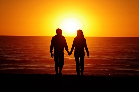 A couple on the beach with sunset background photo