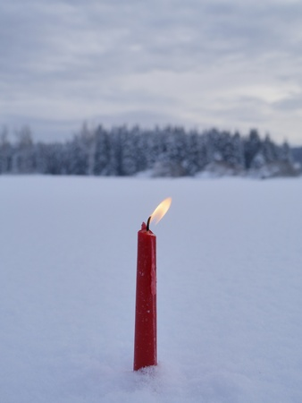 white candle: red candles on white snow background outside in winter Stock Photo