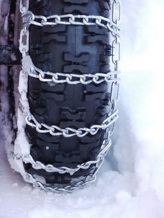Snow chains outside at a wheel in winter photo