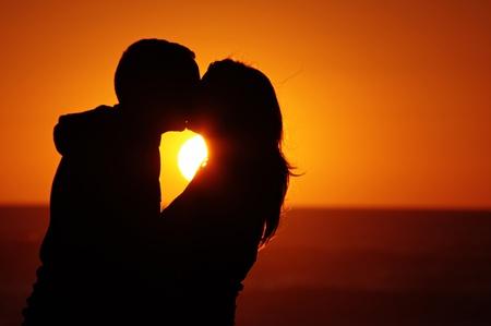 enamorados besandose: Una pareja en la playa con atardecer de fondo Foto de archivo