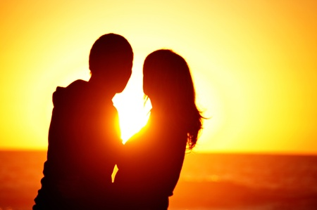 A couple on the beach with sunset background