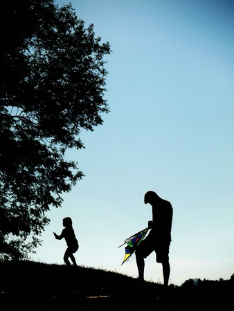 Launching a kite in the sky. Silhouettes man and children. photo