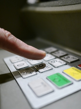 Finger using automatic teller keypad to enter pin number Stock Photo - 17551702