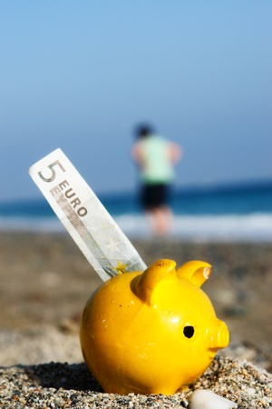economise: close up of a yellow piggybank on the beach