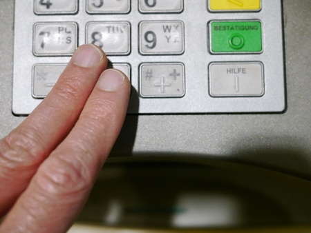 Finger using automatic teller keypad to enter pin number Stock Photo - 17987128