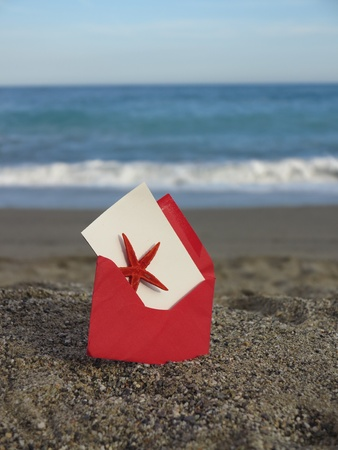 Decorative red  envelope on sand background Stock Photo - 18287651