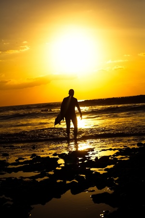 Surfer Walks Down Beach at Sunset photo
