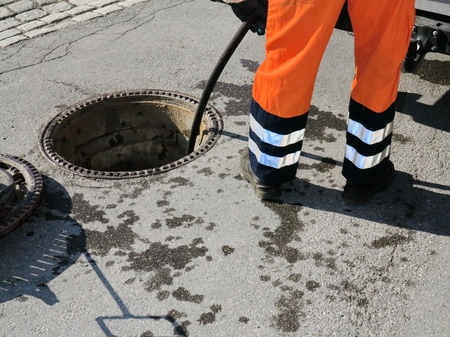 sewer water: sewerage worker  on street cleaning pipe Stock Photo