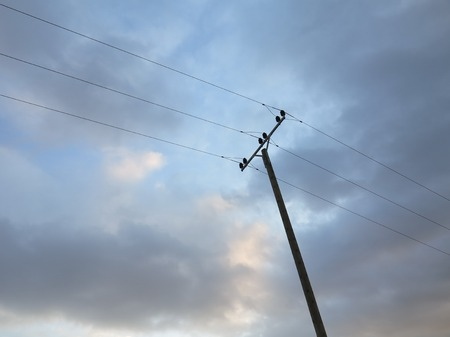 electric power poleagainst a gradient blue sky. photo